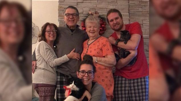 Une famille de quatre personnes avec une grand-maman au centre. Ils sont tous souriants.