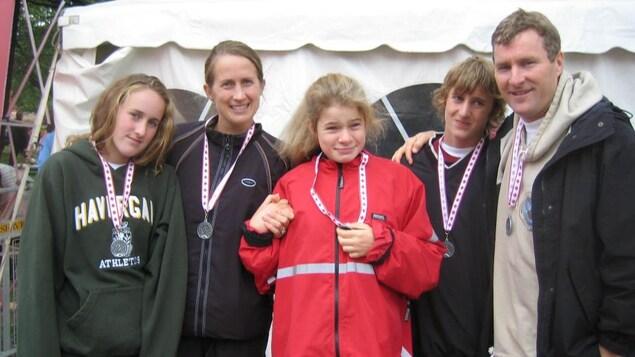 Les cinq membres de la famille, posés devant une tente blanche, portent chacun une médaille.