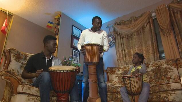 Un père et ses deux enfants jouent du tambour.