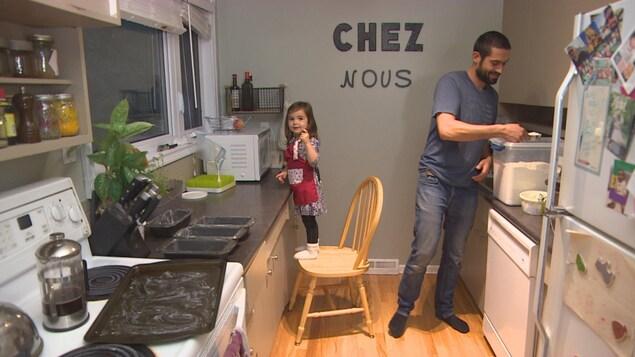 Patrick Lessard prend de la farine dans un contenant transparent et Alizée est debout sur une chaise.