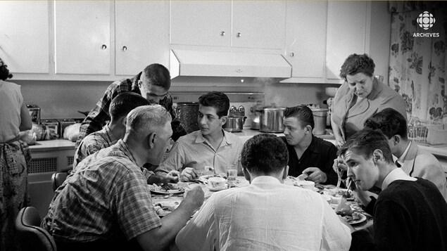 Une famille nombreuse mange sur une table ronde dans une cuisine.