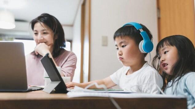 Une mère et ses enfants sont assis devant leurs ordinateurs un jour de pandémie.