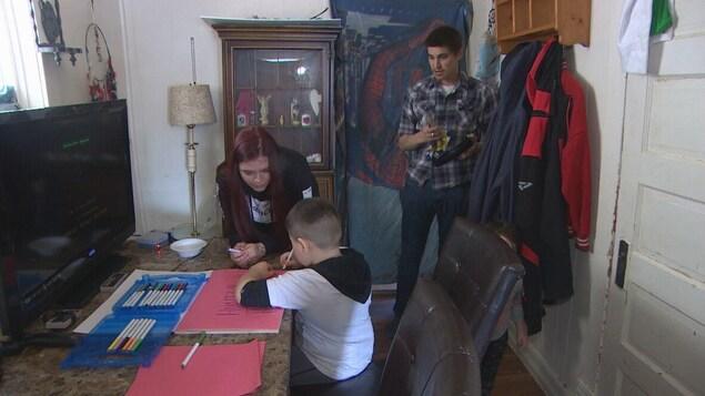 Hunter, 5 ans, fait dos à la caméra, il dessine assis à un bureau. Ses parents, Mélissa et Simon le regardent.