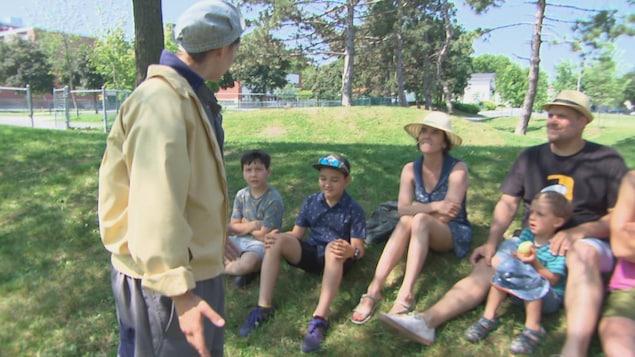 Des familles sont assise dans la pelouse et un comédien leur parle.