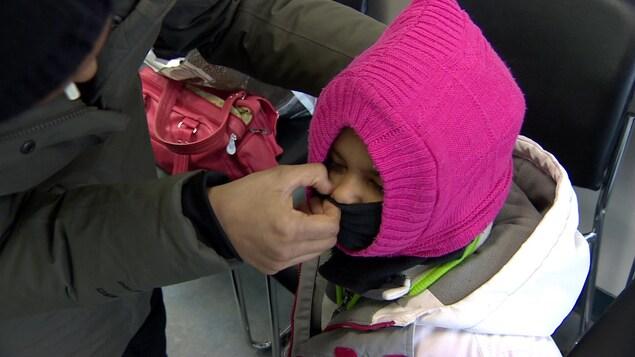 une maman couvre le visage de son enfant couvert par de gros vêtements d'hiver.