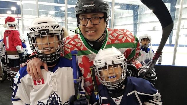 Le portrait de trois personnes prêtes à jouer au hockey
