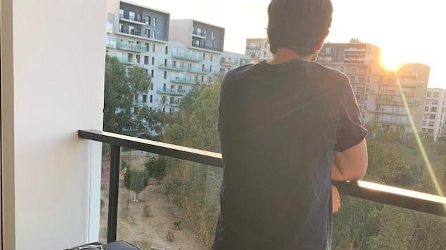 Un homme, installé sur un balcon avec ses valises, regarde le soleil qui se couche derrière les tours d'habitation.