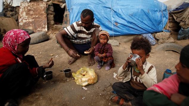 Une famille assise à l'extérieur d'un abri constitué d'une bâche.