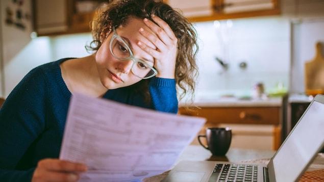 Jeune femme brune lisant ses papiers, l'air stressé.