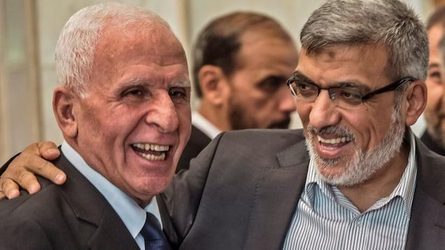 Azzam al-Ahmad du Fatah et le chef du Hamas Izzat al-Rishq rient ensemble après avoir signé un pacte de réconciliation au Caire, jeudi.