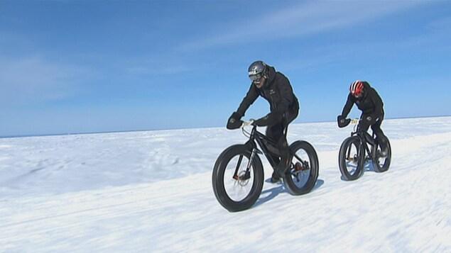 Deux cyclistes vêtus de vêtements d'hiver et de lunettes de ski roulent sur les glaces du lac Saint-Jean.
