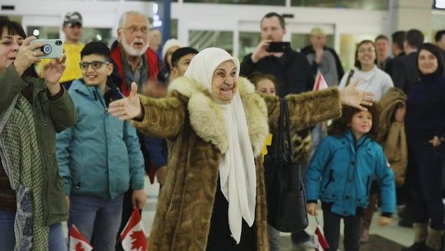 Une femme souriante et les bras ouverts. On voit plusieurs personnes derrière elle.