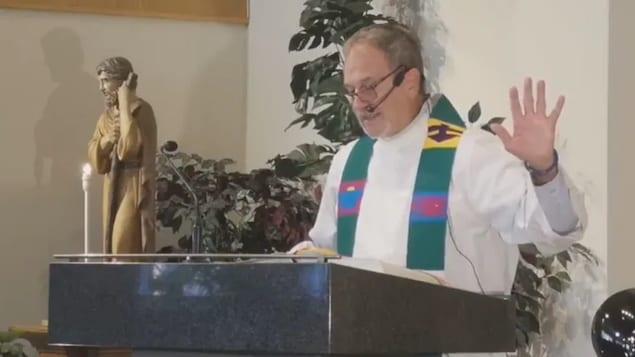 Nagsasalita si Father Rheal Forest sa podium ng simbahan.