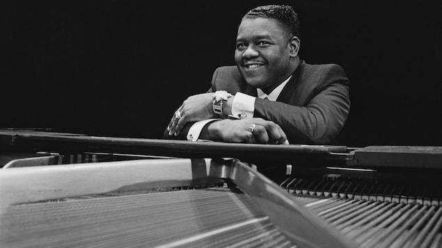 Le pianiste et auteur-compositeur-interprète Fats Domino est assis contre son piano en 1967.