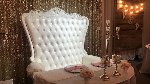 Une chaise capitonnée blanche dans un décor vide de réception de mariage.
