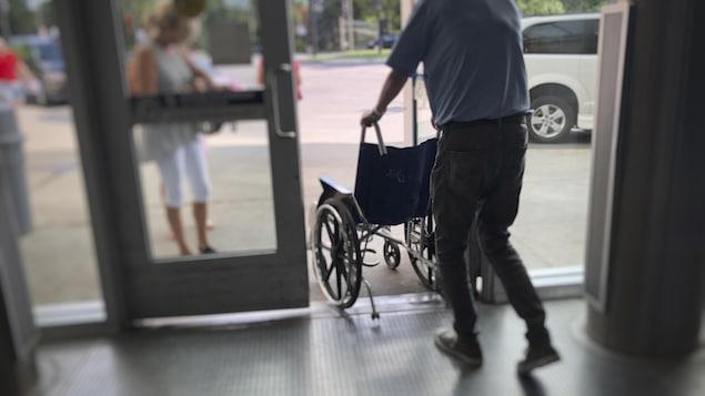 Un homme pousse un fauteuil roulant en passant la porte.
