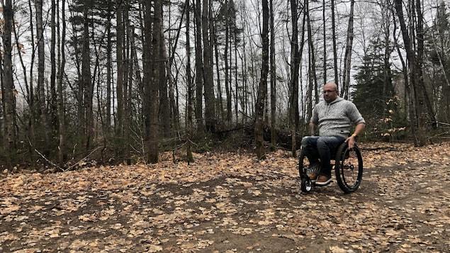 Un homme en fauteuil-roulant dans un sentier.