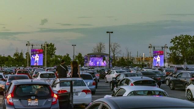 Plusieurs véhicules devant une scène de spectacle.
