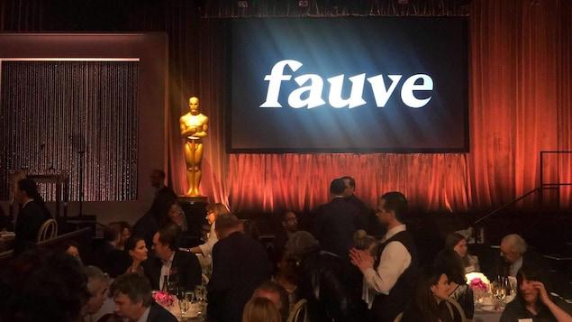 Un écran de cinéma sur lequel est écrit Fauve dans une salle où des personnes sont attablées.
