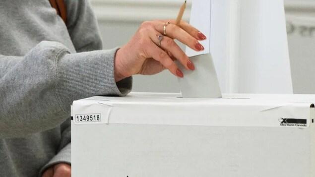 Une personne dépose un bulletin de vote dans une urne.