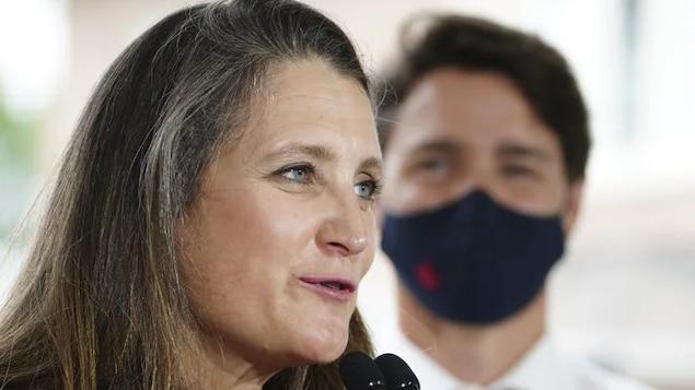 Mme Freeland parle devant un micro sous le regard de Justin Trudeau.