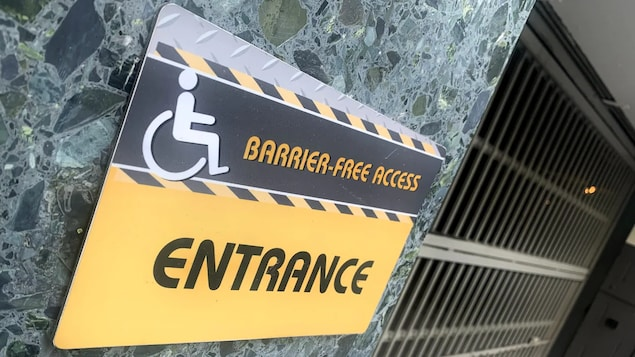 Isang sign sa gilid ng building na nagsasabing barrier-free access, entrance.