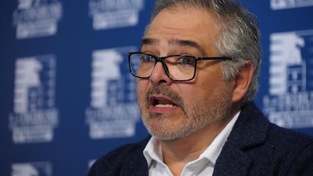 Un homme s'adresse aux médias en conférence de presse.
