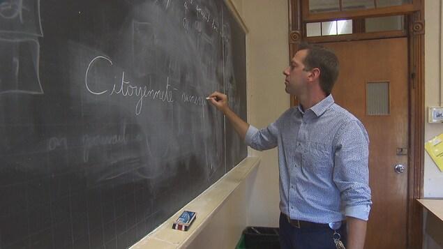 Un homme écrit sur un tableau les mots citoyenneté et numérique.
