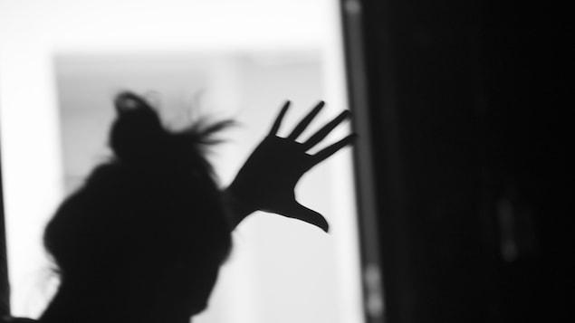 Une femme dont on ne voit que l'ombre met la main sur une fenêtre.