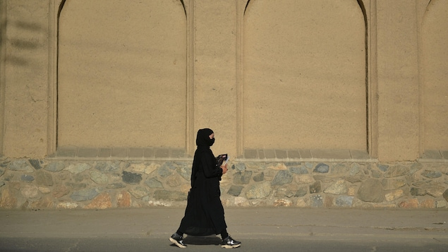 Une femme en burqa, tout en noir, marche dans une rue vide de Kaboul.