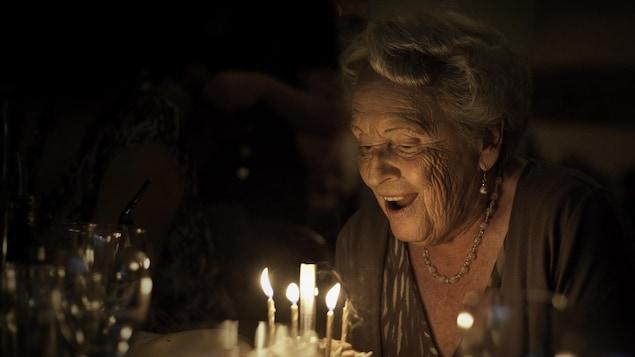 Une femme souffle les bougies de son gâteau de fête.