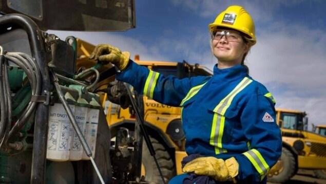 Une femme en habit de construction pose devant de la machinerie lourde