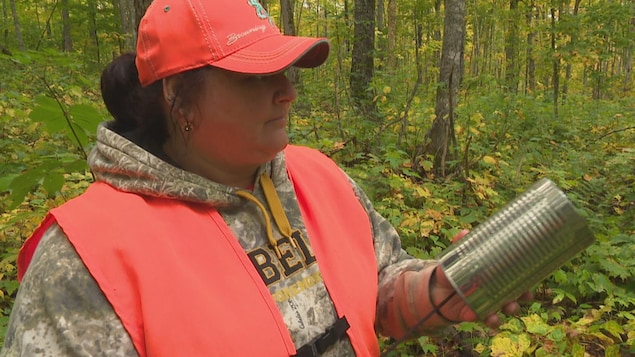 Une jeune femme coiffée d'une casquette et d'une veste de sécurité, dans une forêt.