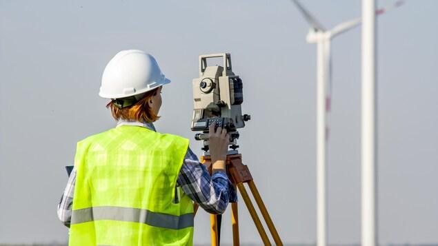 Une arpenteuse-géomètre dans un champ fait des mesures devant une éolienne.
