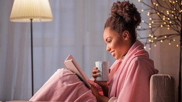 Une jeune femme lit un livre, assise dans un sofa avec une tasse dans la main.