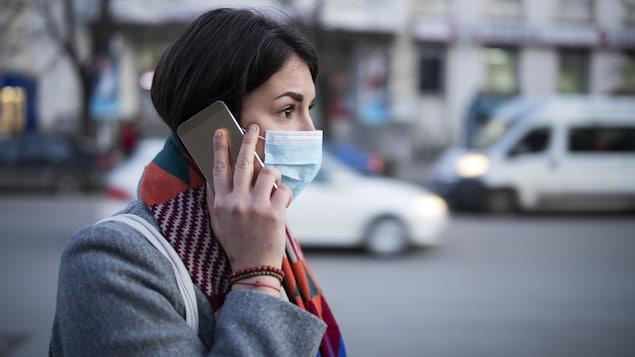 Une femme portant un masque marche dans la rue en parlant au téléphone.