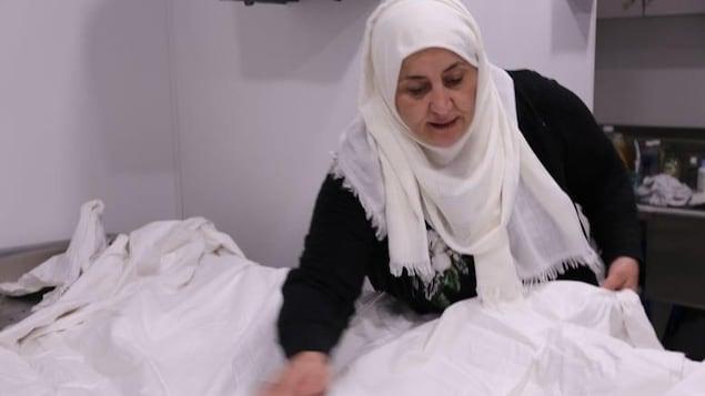 Une femme tenant un kafan, un vêtement traditionnel utilisé lors des funérailles.