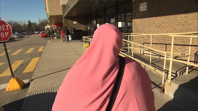 Une femme portant un niqab rose marche sur la rue.