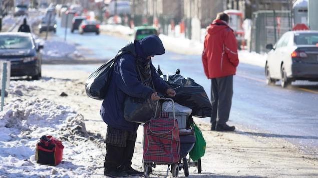 Une femme sans-abri transporte des sacs sur un chariot.