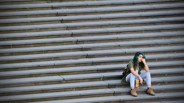 Une jeune femme est assise seule dans les marches d'un parc.