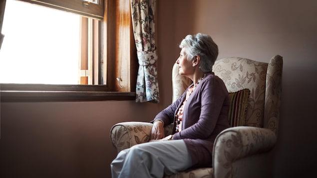 Une femme seule regarde par la fenêtre.