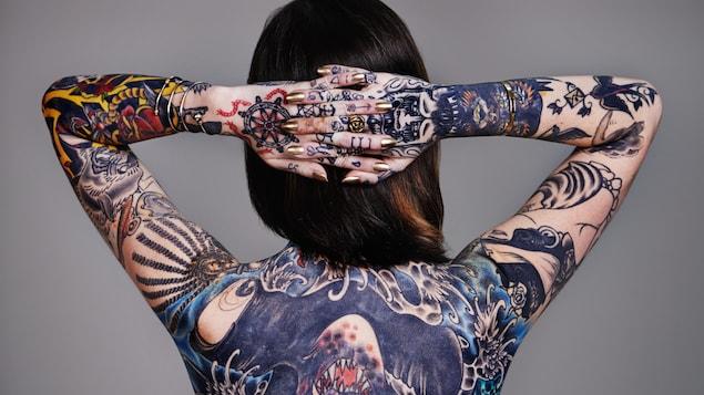 On voit une femme, de dos, les mains jointes derrière la tête, qui expose les tatouages qu'elle a sur le corps.