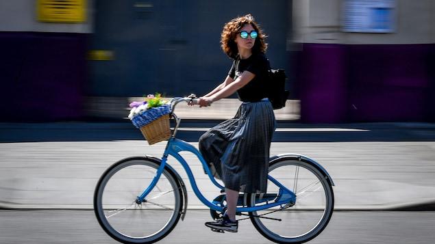 Une femme circule à vélo dans la rue