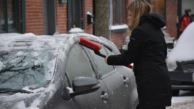 Une femme gratte du verglas sur sa voiture.