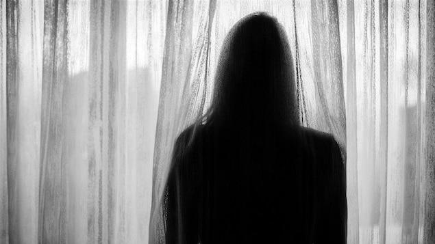 Une femme de dos regarde par la fenêtre derrière un rideau.