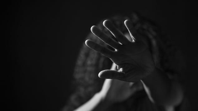 Une femme se cache le visage avec sa main.