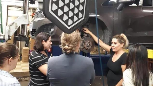 Des femmes qui suivent un cours sur la mécanique automobile.