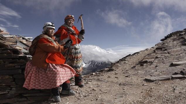 Deux femmes portant un casque, des pioches et des lampes de mineurs se tiennent sur une pente rocailleuse.