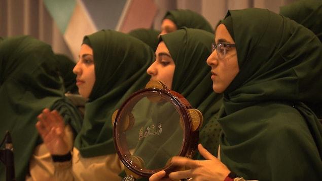 Des femmes musulmanes voilées jouent avec des instruments de musique lors d'un rassemblement dans une salle de réception à Laval.