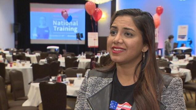 Rina Shah pose dans une grande salle. Derrière elle, «National Training» (ou «Formation nationale») est inscrit sur un écran.